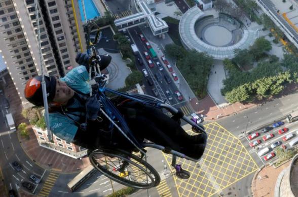 В Гонконге мужчина на инвалидной коляске поднялся на небоскреб в благотворительных целях